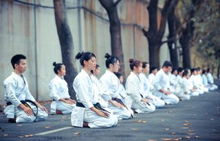 group of martial artists sitting on the ground by Thao Le Hoang